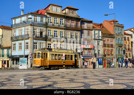 Low angle capture of Porto tour Tram going through the city street showing the typical Portuguese architecture. in Porto, Portugal - Stock Photo