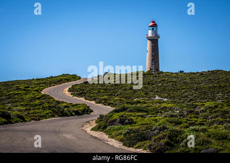 Lighthouse with red top and winding road at Cape du Couedic on Kangaroo island in SA Australia - Stock Photo
