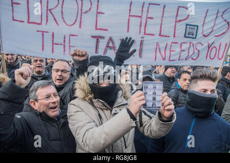 Madrid, Spain. 28th January 2019. Hundreds of taxi drivers protest againts Uber and cabify in Madrid, Puerta del sol. In the picture a guy with a mask taking a paper with the photos of responsible of cabify and uber, people of the government in Madrid. In front of the city council of Madrid, Spain. Credit: Alberto Sibaja Ramírez/Alamy Live News - Stock Photo