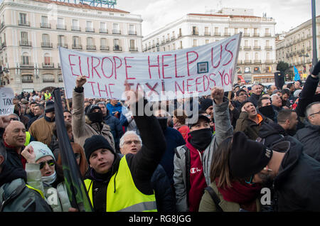 Madrid, Spain. 28th January 2019. Taxi drivers in Madrid have been on a strike for more than a week demanding the prohibition of Uber and Cabify in the Spanish capital-city.   Due to a lack of agreement, hundreds of taxi drivers protested at Puerta del Sol, Madrid's central square.  In the picture taxi drivers are raising their fists to protest. Credit: Lora Grigorova/Alamy Live News - Stock Photo