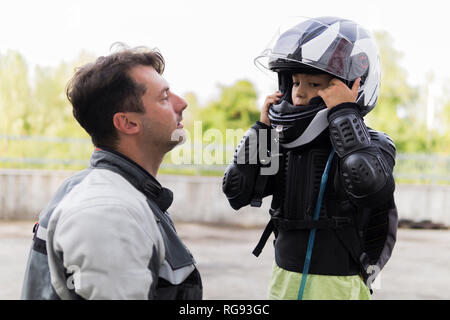Father watching son putting on motorcycle helmet - Stock Photo