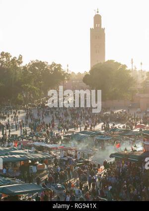 Atmospheric shot of Jemaa el-Fnaa market in Marrakesh as the sun goes down - Stock Photo