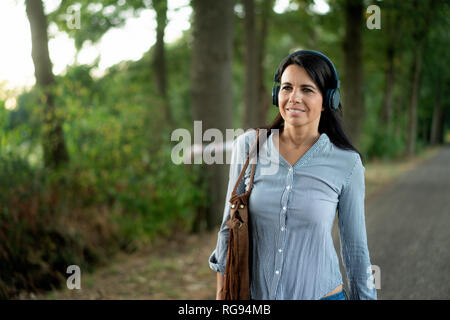 Smiling woman wearing headphones walking on country road - Stock Photo