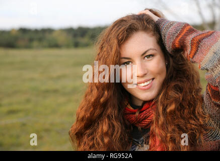 Portrait of redheaded young woman in autumn - Stock Photo