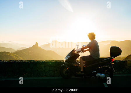 Spain, Canary Islands, Gran Canaria, man on motor scooter watching sunset over mountainscape - Stock Photo