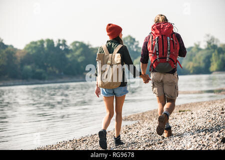 Rear view of young couple with backpacks walking hand in hand at the riverside