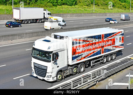 Looking down from above side & front view white hgv lorry truck & Aldi food supply chain articulated trailer side union flag graphics on UK motorway - Stock Photo