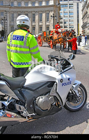 UK motorbike & metropolitan police officer blocking road at Admiralty Arch while horse drawn State Landau carriage completes formalities London UK - Stock Photo