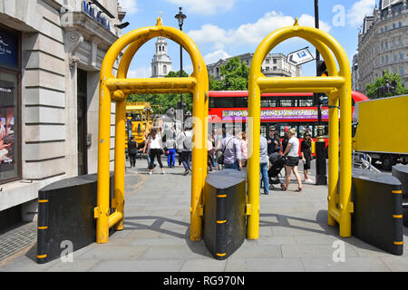 Yellow steel arches beside pivotable anti terror security barriers on pavement help with crowd control & anti vehicle terrorism in London England UK - Stock Photo