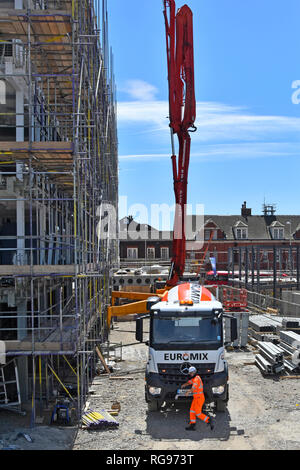 Euromix delivery lorry truck & driver pouring concrete into vertical pumping boom rig to roof level  on confined construction building site London UK - Stock Photo