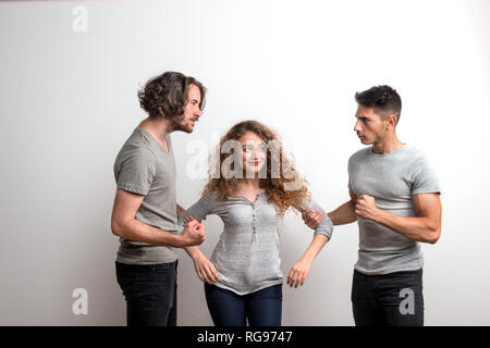 Two angry guys fighting over a girl, a studio shot. - Stock Photo