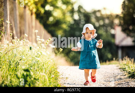 Portrait of baby girl walking outddors in summer