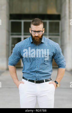 Portrait of bearded hipster businessman wearing glasses and plaid shirt - Stock Photo
