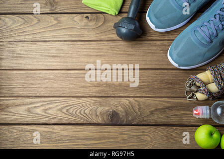 Fitness and healthy active lifestyle dieting background concept. Dumbbell, jump ropes, apples, sport shoes, bottle of water and green apples on wood b - Stock Photo