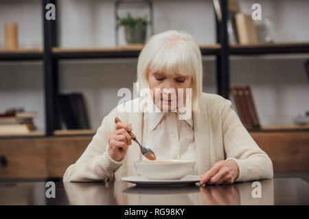 sad lonely senior woman sitting at table and eating at home - Stock Photo