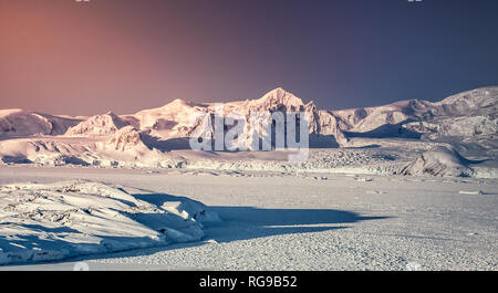 Sunset in Antarctica. Snow on mountain range against colorful pink and blue sky. Big glacier in front. Nature background. Stunning winter landscape. T - Stock Photo