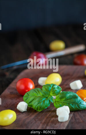 Fresh from the garden basil and heirloom tomatoes with mozzarella cheese for caprese salad, Italian food and healthy vegetarian diet concept, over a r - Stock Photo