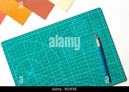 Paper artwork scrapbooking background. Green cutting mat and knife with colored paper on white table - Stock Photo