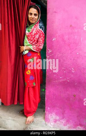 India. Bihar. Muzaffarpur.Purani Gudri (old slum). A young woman wearing colourful shawar kameez looks out from a red curtained doorway. - Stock Photo