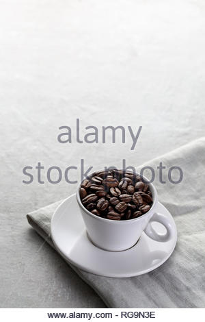 A white coffee cup and saucer on a cloth filled with coffee beans with space for copy text - Stock Photo