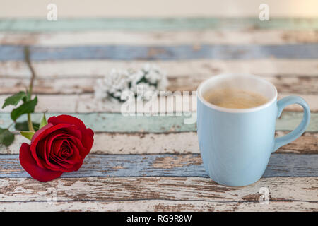Coffee in turquoise mug with single red rose and flowers on wooden table - Stock Photo