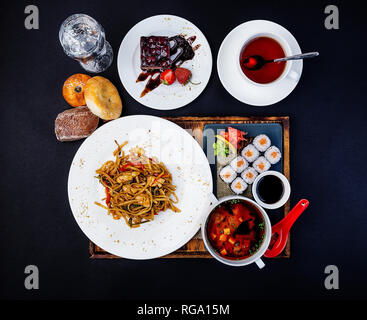 Asian food set. Fried noodles with chicken, miso soup, sushi with salmon, cup of tea and cake. - Stock Photo