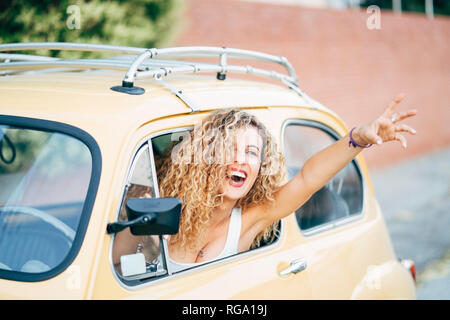Portrait of happy blond woman leaning out of window of classic car showing victory sign - Stock Photo