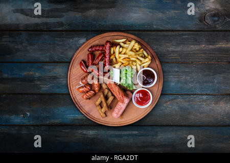 Beer snacks set. Grilled sausages and french fries served with tomato and BBQ sauce. - Stock Photo