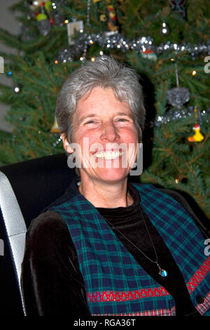 woman; portrait; wide smile; greying hair; Christmas tree; happy; attractive, vertical; MR - Stock Photo
