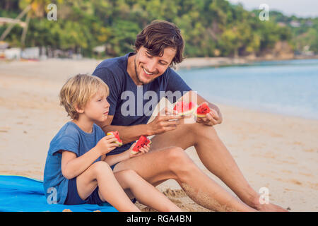 Happy family Father and son eating a watermelon on the beach. Children eat healthy food. - Stock Photo