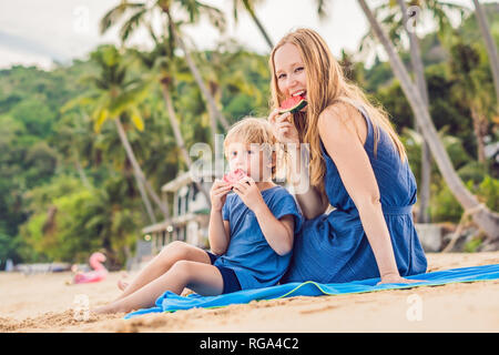 Happy family mother and son eating a watermelon on the beach. Children eat healthy food. - Stock Photo