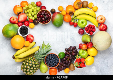 Heart made from healthy colorful fruits, strawberries raspberries oranges plums apples kiwis grapes blueberries mango persimmon pineapple on the white - Stock Photo