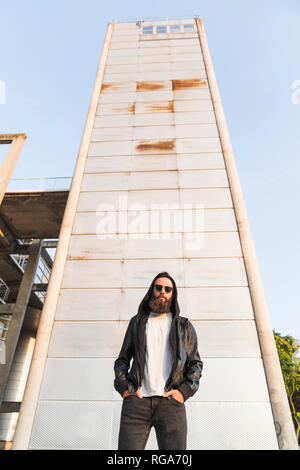 Cool bearded young man wearing sunglasses and hooded jacket standing in front of a tower - Stock Photo