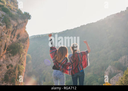 Spain, Alquezar, rear view of two young women on a hiking trip cheering - Stock Photo