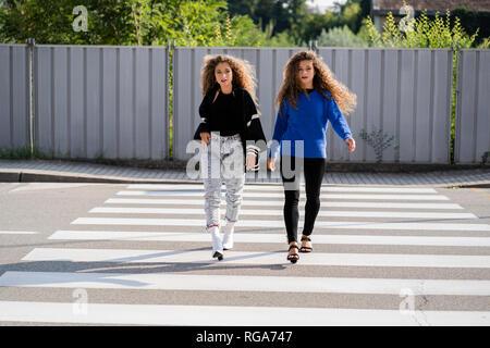 Twins walking on zebra crossing - Stock Photo