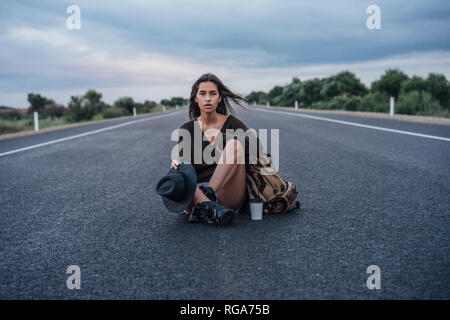 Portrait of hitchhiking young woman with backpack and beverage sitting on lane - Stock Photo