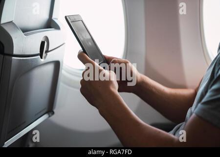 Man using ebook in airplane - Stock Photo