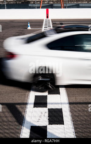 Car crossing finishing line on racetrack - Stock Photo
