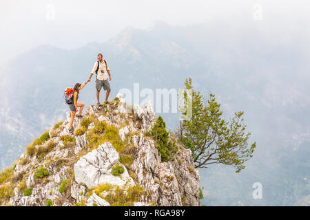 Italy, Massa, man helping woman to climb on top of a peak in the Alpi Apuane mountains - Stock Photo