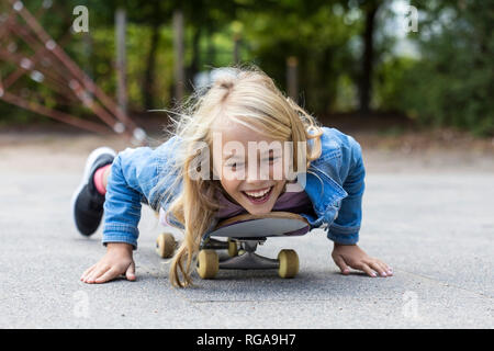 Portrait of laughing blond girl lying on her skateboard outdoors - Stock Photo