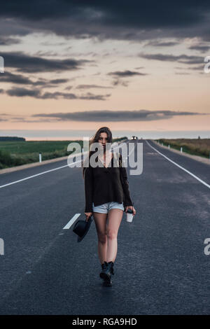Portrait of hitchhiking young woman with backpack and beverage walking on lane at evening twilight - Stock Photo