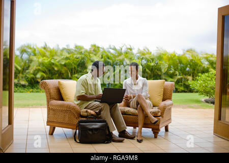 Couple checking their emails on a laptop. - Stock Photo