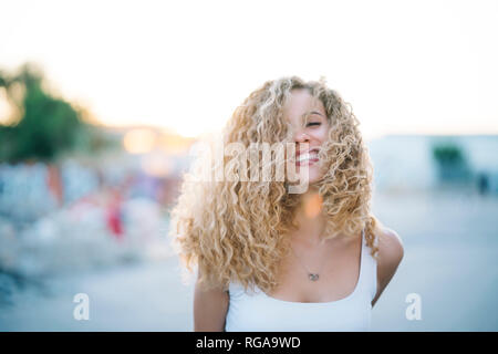 Portrait of happy young woman with blond ringlets