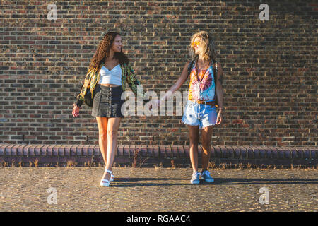 Two young women holding hands in front of brick wall - Stock Photo
