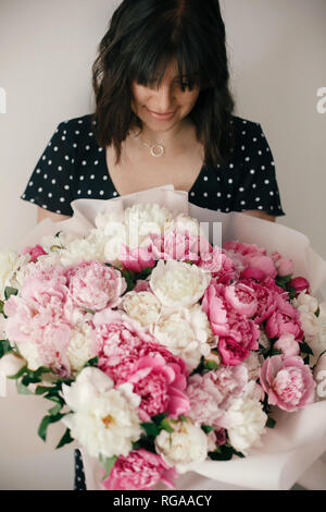 Beautiful brunette girl in vintage dress holding big bouquet with pink and white peonies. Happy stylish woman with peony flowers in room. Internationa - Stock Photo