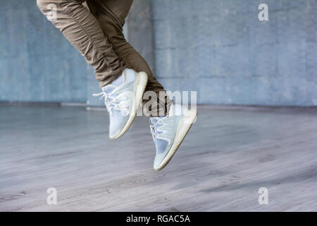 Break dance guy is jumping. Freestyle dancer in movement on grey background, cropped image. - Stock Photo