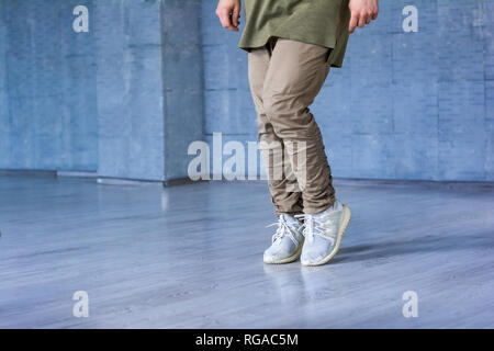 Dancer on grey background, cropped image. Hip-hop dancer wearing grey cotton trousers and sneakers on grey background. Sreet style dancing. - Stock Photo