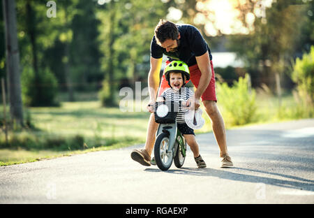 Father teaching little son riding bicycle - Stock Photo