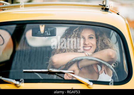 Portrait of happy blond woman in a classic car - Stock Photo