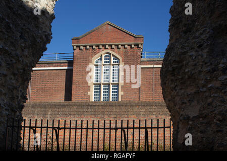 The main Victorian building of Reading Prison viewed through the ruins of Reading Abbey, Berkshire - Stock Photo